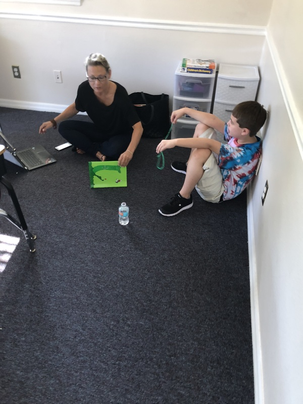 teacher and a student sitting on the floor